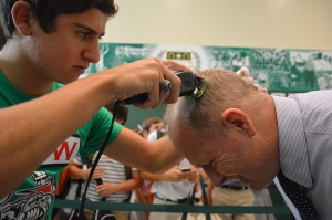 Concentrating, Fredy Mattioli '15 shaves Mr. Healey's head during Spirit Week. Photo: MAGIS