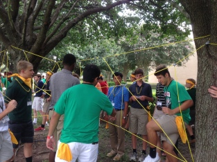 Crusader Crew Leaders Christian Hernandez (Left) and Camden Andarsio (Right) help their freshman House configure the best path through the spiderweb, a team-building exercise during the 2014 Freshman Orientation. Photo: MAGIS